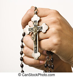 Prayer beads. - Woman\'s hands holding rosary with crucifix.