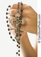 Woman holding crucifix. - Woman\'s hands holding rosary with...