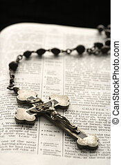 Christian symbols - Rosary with crucifix lying on open Bible...
