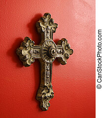 Ornate cross. - Ornate religious cross hanging on red wall.