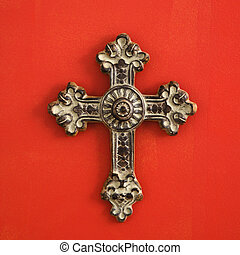 Religious cross - Ornate religious cross hanging on red wall...