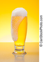 Overflowing pale lager beer - Glass full of tasty...