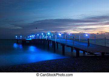 Wooden pier on the sea, after sunset