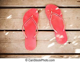 Pink flip flop sandals on wood background