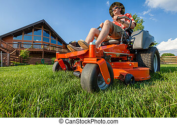 Riding lawnmower - A man is mowing backyard on a riding zero...