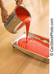 Woman pouring paint. - Caucasian woman pouring red paint...