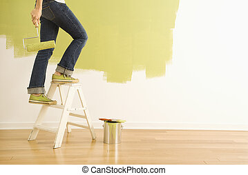 Woman painter on ladder - Legs of woman climbing stepladder...