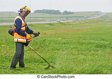 lawn mower worker man cutting grass in green field