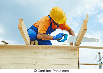 carpenter works with hand saw - construction roofer...