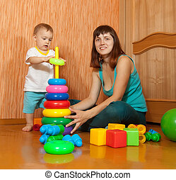 Happy mother and baby plays at home