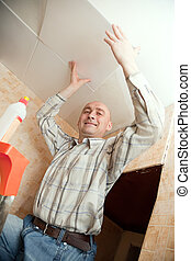 man glues ceiling tile at home - Smiling man glues ceiling...