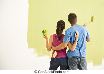 Couple painting home. - Attractive couple standing in front...