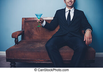 Happy businessman on sofa drinking cocktail