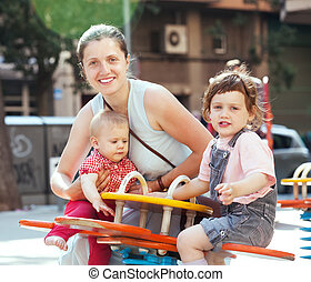 Happy woman with children on swings in playground