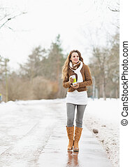 Happy young woman with cup of hot beverage walking in winter park