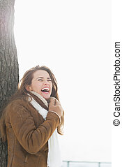 Smiling young woman leaning against tree in winter park