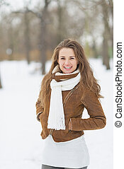 Portrait of happy young woman in winter park