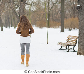 Woman walking in winter park rear view