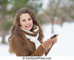 Smiling young woman with cell phone in winter outdoors