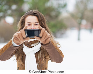 Young woman taking photo using cell phone in winter park