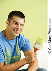 Man painting wall - Smiling man kneeling in front of...