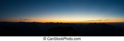 panorama of austrian mountains at sunset with blue orange sky
