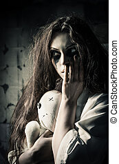 Horror style shot: strange sad girl with moppet doll in...