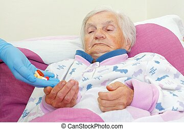 Retired life - Elderly woman takes pills from a nurse