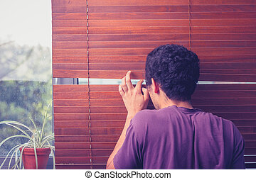 Young man peeping out through venetian blinds