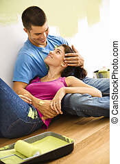 Couple taking break - Couple sitting on floor embracing...