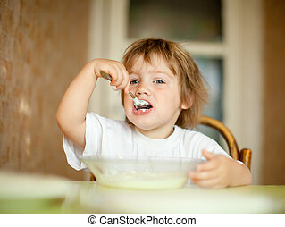 child eats with spoon   - child eats with spoon in home