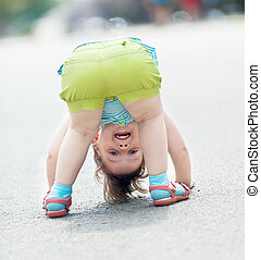 girl playing upside down - three-year baby girl playing...