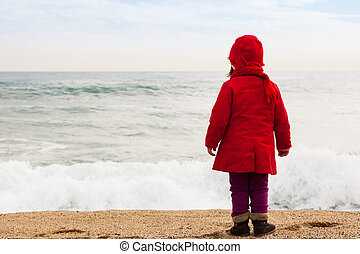 Baby girl in cold windy day - Baby girl on sand beach in...