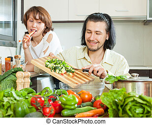 Cute couple preparing a meal of vegetables in your home