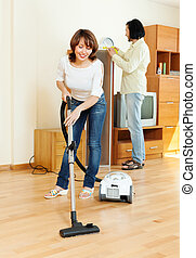 Happy woman and man doing housework together in home