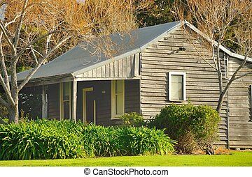 group settlement house - old weatherboard house amid trees...