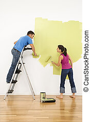 Couple painting house. - Attractive young adult couple...