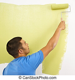 Man painting wall - Man painting over white wall with green...