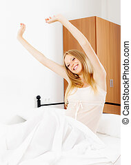 Happy woman awaking on white sheet in her bed at home