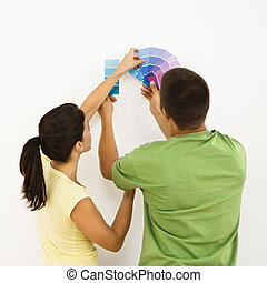 Couple choosing home color. - Attractive young adult couple...