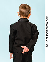 Crossed fingers - Boy have fingers crossed behind back,...