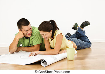 Couple planning future - Attractive young adult couple lying...