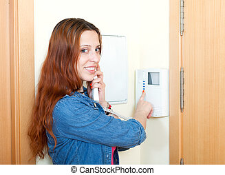 Young woman using house videophone indoor - Young woman...