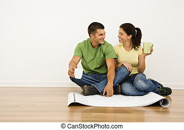 Couple renovating - Attractive couple sitting on home floor...