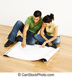 Couple reading blueprints - Attractive young adult couple...