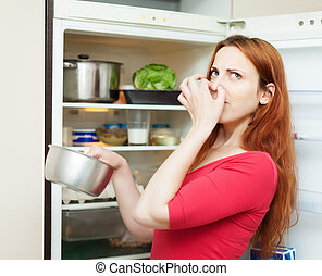 woman in red holding foul food near   refrigerator