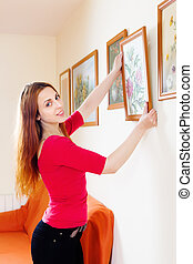 Positive woman in red hanging the art pictures on wall at...