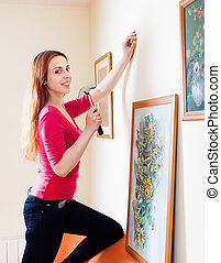 Positive  woman hanging the art pictures