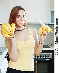 girl eating banana at kitchen - girl eating banana at home...
