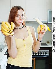 girl eating banana at kitchen - girl eating banana at home...